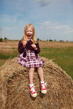 Happy little blonde girl playing in the hay Royalty Free Stock Images