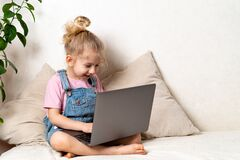 Happy little blonde girl sits at home on a bed with a laptop, a place for text, the concept of learning at home