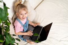 Happy little blonde girl sits at home on a bed with a laptop, a view from above, a place for text, the concept of learning at home