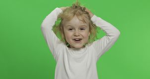 Happy little blonde girl in white t-shirt. Cute blonde child. Making faces stock image