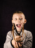 Happy little boy. Child who just received a slingshot on his birthday Royalty Free Stock Image