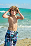 Happy little boy on the beach. Shot of a happy little boy on the beach Stock Photo