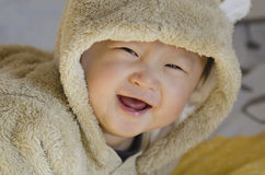 Happy Little Boy in Bear Clothes with Big Smile. Crawling on bed, look at camera Royalty Free Stock Photography