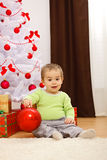 Happy little boy with big Christmas ornament. Happy little boy sitting in front of Christmas tree, holding big red ornament stock images