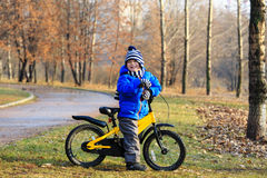 Happy little boy with bike in autumn park Royalty Free Stock Photo