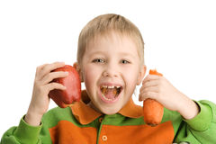 Happy little boy biting apple and carrot stock image