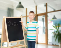 Happy little boy with blackboard and chalk. People, childhood, mathematics and education concept - happy little boy with blackboard and chalk writing math Royalty Free Stock Photography