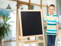 Happy little boy with blank blackboard Stock Images