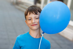 Happy little boy with blue air balloon Stock Images
