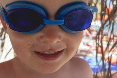 Happy little boy with blue diving glasses and grains of sand on. His face, enjoying in summer activities. Family trip and vacation concept royalty free stock image
