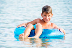 Happy little boy with blue life ring has fun Stock Images