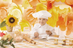 Happy little boy with a book chef preparing Breakfast in the kit Stock Photo