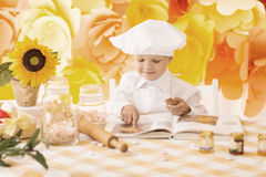 Happy little boy with a book chef preparing Breakfast the kit Royalty Free Stock Photo