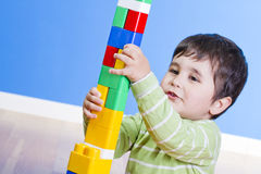 A happy little boy is building a colorful toy Royalty Free Stock Images