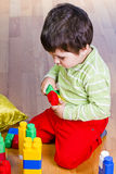 A happy little boy is building a colorful toy Royalty Free Stock Photo
