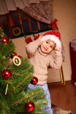Happy little boy in a cap of Santa Claus standing near a Christm Stock Photo