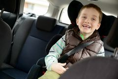 Happy little boy in car safety seat. Stock Image