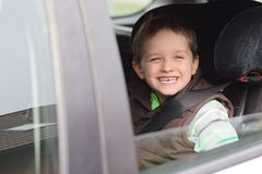 Happy little boy in car safety seat. Royalty Free Stock Images