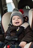 Happy little boy in car seat Stock Images