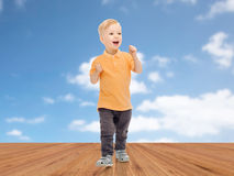 Happy little boy in casual clothes. Childhood, fashion, emotion, expression and people concept - happy little boy in casual clothes having fun over blue sky and Stock Photos