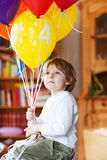 Happy little boy celebrating his 4 birthday with colorful balloo Stock Photos