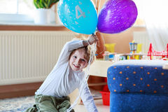 Happy little boy celebrating his 4 birthday with colorful balloo Royalty Free Stock Images