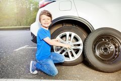 Happy little boy changing tyre of car outside Stock Photos