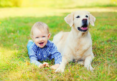 Happy little boy child and Golden Retriever dog lying together on grass. In park royalty free stock image