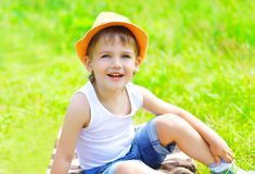 Happy little boy child in hat sitting on the grass in summer Stock Photos