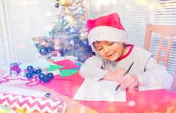 Happy little boy writing letter to Santa Claus royalty free stock photography