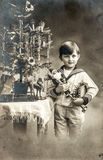 Happy little boy with christmas tree, gifts and vintage toys. Antique sepia picture with original film grain and scratches stock photography