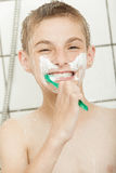 Happy little boy cleaning his teeth in the shower Stock Photos