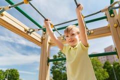 Happy little boy climbing on children playground Stock Images