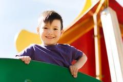Happy little boy climbing on children playground Stock Photos
