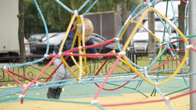 Happy little boy climbing on playground equipment stock video
