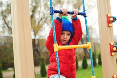 Happy little boy climbing the rope wall outdoors. Kid playing games on colorful playground in cold weather. Autumn, childhood, lei stock image