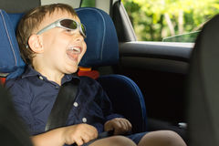 Happy little boy clowning around. Laughing as he sits in his child seat in the back of the car wearing trendy modern sunglasses royalty free stock images