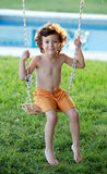 Happy little boy with curly hair sitting on a swing Royalty Free Stock Photos