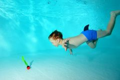 Happy little boy dives for a toy under the water in the pool and smiles. Portrait. Horizontal view Stock Photo
