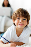 Happy little boy drawing lying on the floor Stock Photography