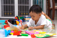 Happy little boy drawing and reading royalty free stock photos