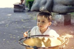 Happy little boy drinking water from fountain in the city park o Royalty Free Stock Photo