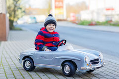 Happy little boy driving big toy car and having fun, outdoors Royalty Free Stock Photography