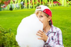 Happy little boy eating cotton candy Stock Photos