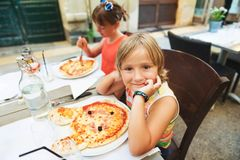 Happy little boy eating kid`s pizza in the restaurant. Menu for children, animal shaped italian pizza for youngsters stock photo