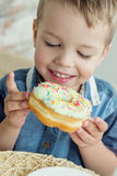 Happy little boy eats the sweet Royalty Free Stock Photos
