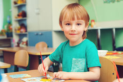 Happy little boy engaged in art and craft in classroom . Happy little boy engaged in art and craft in a classroom stock photos