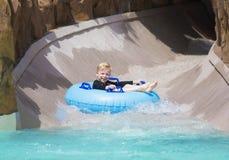 Happy little boy enjoying a wet ride down a water slide. Smiling cute little boy having fun while enjoying a fun ride down a water park water slide on a blue Stock Photo