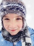 Happy little boy enjoying winter day in nature with falling snow