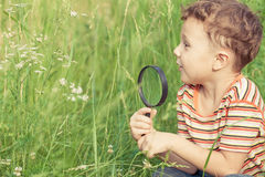 Happy little boy exploring nature with magnifying glass Royalty Free Stock Photography